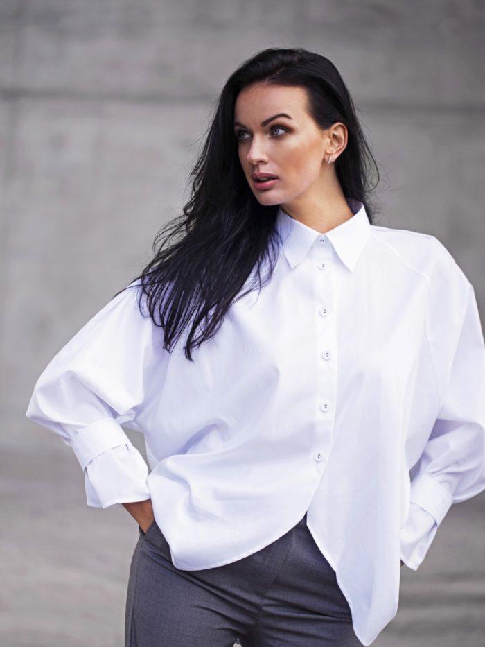 Mannequin portant une chemise blanche en ample sur un fond bétonné.