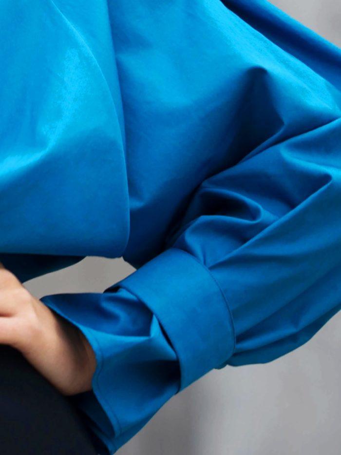 Gros plan d'un bras. Détail d'une manche bleu vert