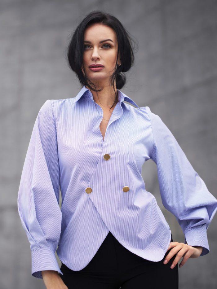 mannequin sur fond gris, portant une chemise bleu et blanche.