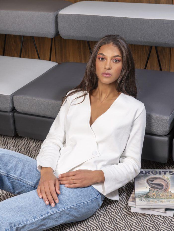 Jeune femme assise sur le sol, au pied d'un fauteuil. Des livres et des magazines sont déposés sur sa gauches.